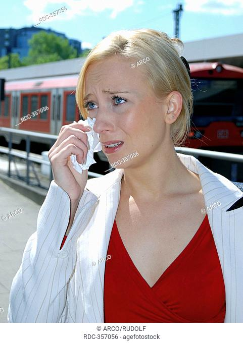 Young woman at rail station, train track