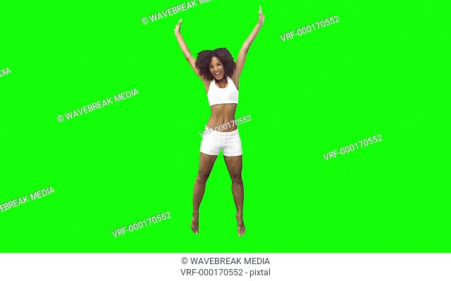 Brunette in slow motion performing a starfish jump against a green background