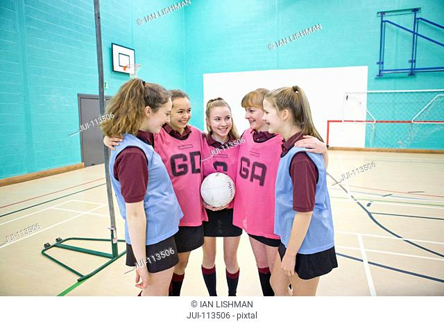 Smiling high school students in huddle before netball game