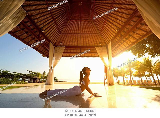 Pacific Islander woman practicing yoga in gazebo on beach