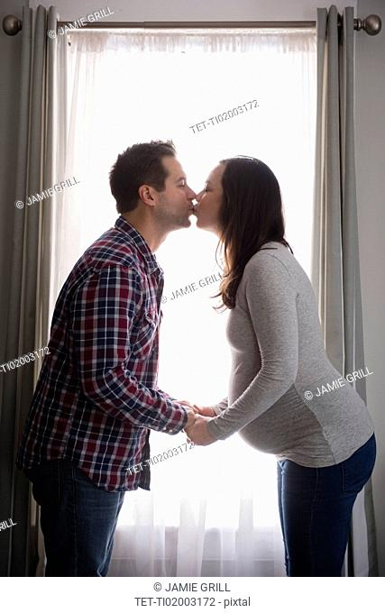 Mid adult couple kissing in front of window