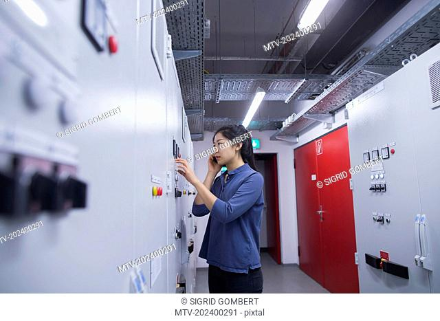 Young female engineer updating control panel using mobile phone in an industrial plant, Freiburg im Breisgau, Baden-Württemberg, Germany