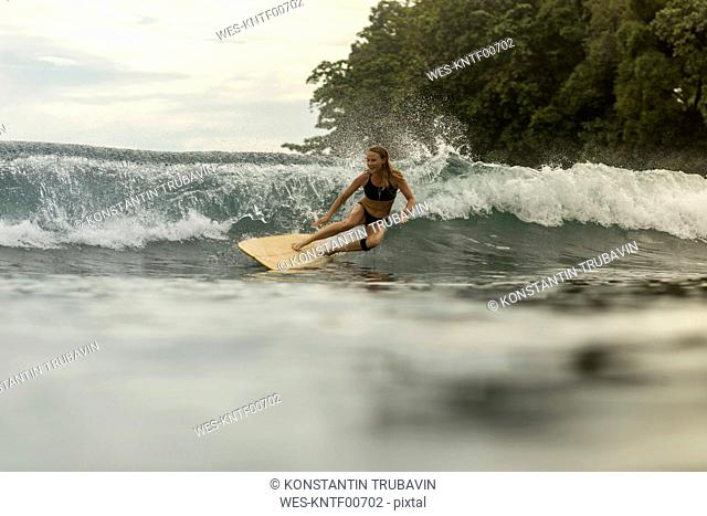 Indonesia, Java, happy woman surfing