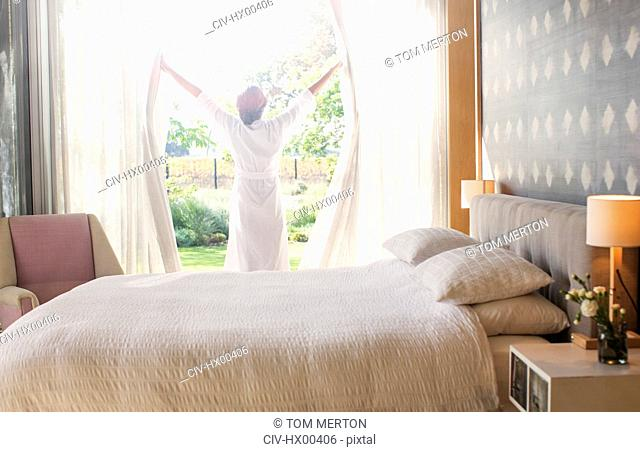 Woman in bathrobe opening bedroom curtains