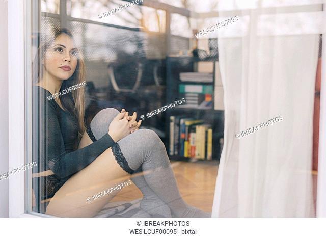 Young woman sitting on the floor of living room looking through balcony door