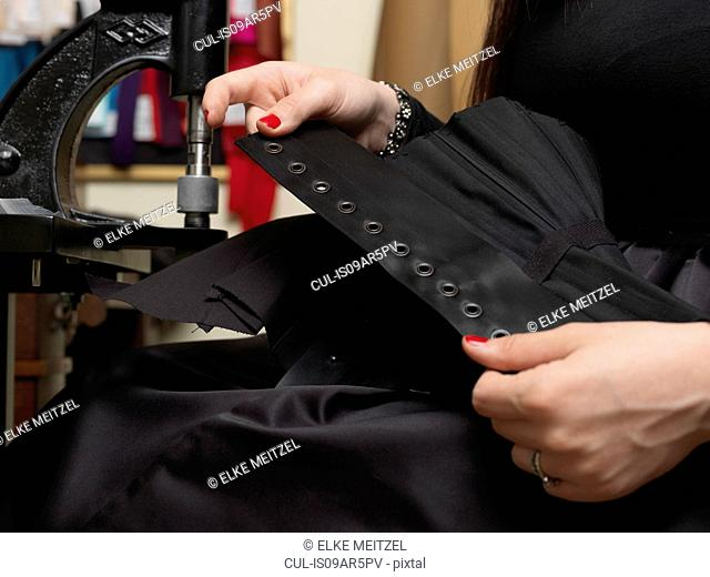 Corset maker holding up corset