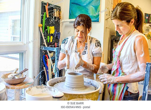 Female potter explaining to mature student making pot on potters wheel