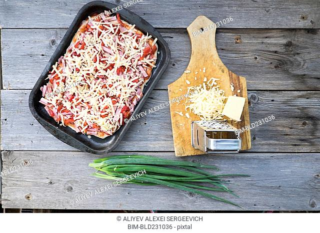 Cheese on cutting board near tray of pizza