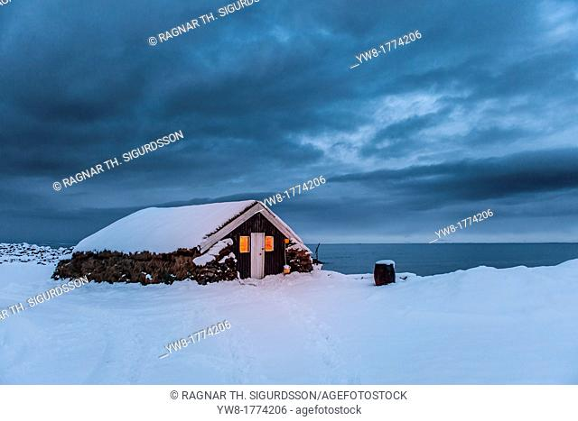 Old farmhouse with turfed roof in the winter, Skagafjordur, Iceland