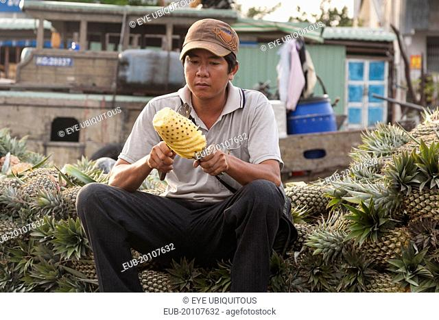 Man cutting a pineapple in the floating market at Cai Rang near Can Tho