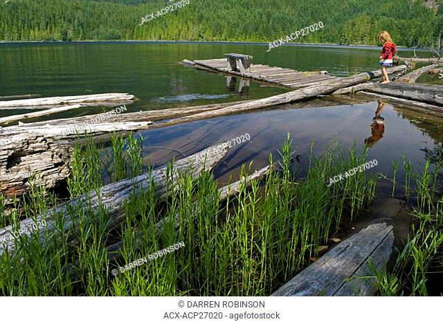 Young girl walks on the dock at Rainy Day Lake near Powell River on the beautiful Sunshine Coast of British Columbia, Canada