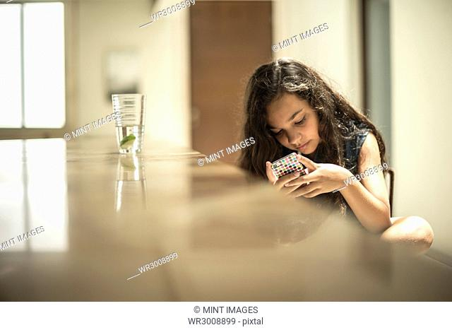 A girl sitting looking at a mobile phone screen