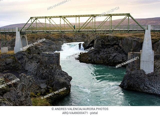 Female hiker crossing bridge over river, Iceland