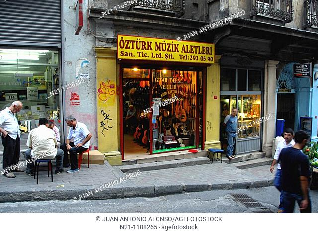 Men playing Backgammon beside one of the many instruments shops on the Yuksek Kaldirim Caddesi, a steep street leading to the Galata Kulesi