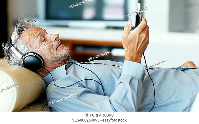 A handsome senior man lying on the sofa with his mp3 player
