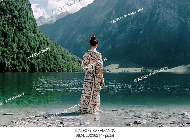 Caucasian woman wading in mountain lake