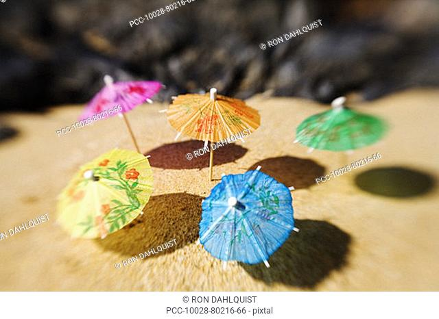 Colorful cocktail umbrellas stuck in the sand of a tropical beach
