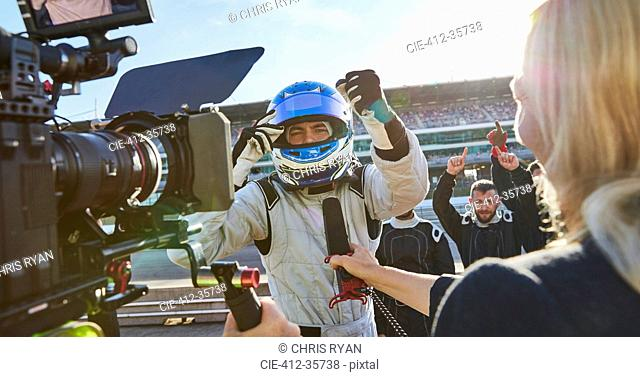 News reporter and cameraman interviewing formula one driver cheering, celebrating victory