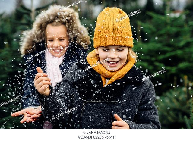 Brother and sister having fun with snow before Christmas