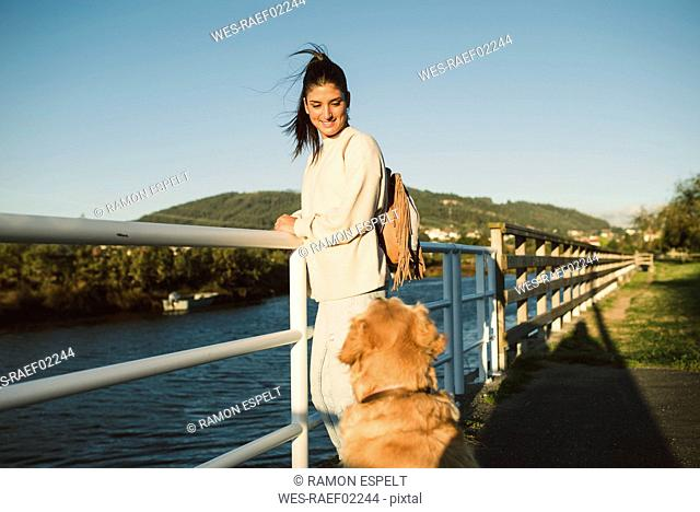 Smiling young woman looking at her dog at the waterfront
