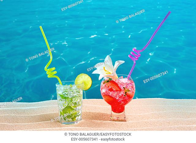 Mojito and strawberry cocktails on white sand beach and turquoise sea