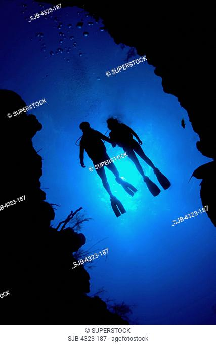 Two Divers Silhouetted Above a Reef Crevice