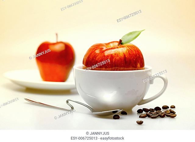 apple in a cup, saucer, spoon and coffee beans
