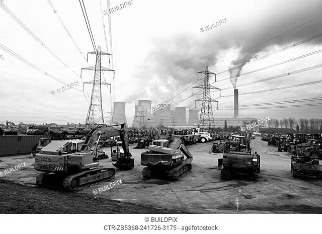 Plant hire equipment for sale on auction yard with power station in background, England, UK