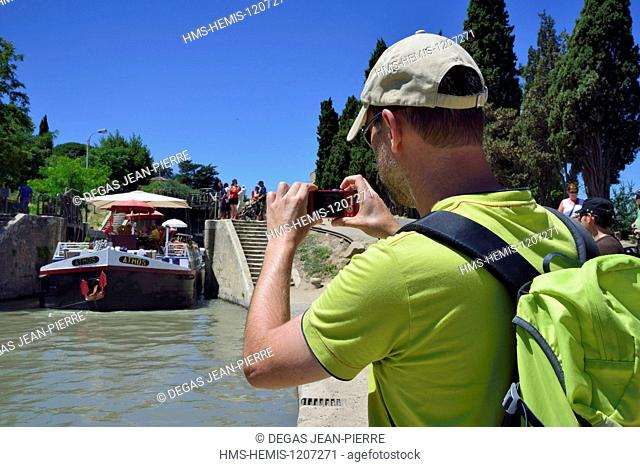 France, Herault, Beziers, Canal du Midi listed as World Heritage by UNESCO, locks of Fonseranes, tourist photographing a barge at the exit of an airlock