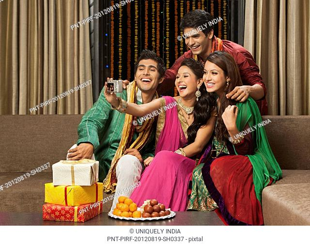 Friends taking a picture of themselves with a camera on Diwali