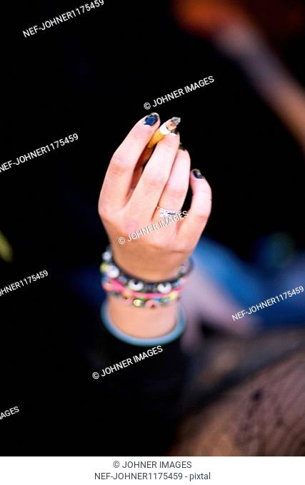Hand of teenage girl holding cigarette