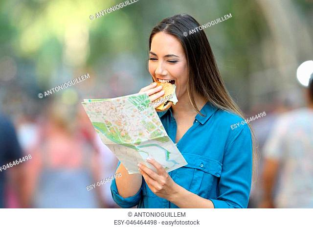 Happy tourist eating a burger and reading a paper map on vacation in the street