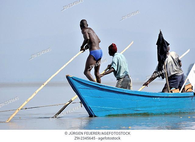 Fishers pushing their boat through the water at Lake Victoria, Kenya