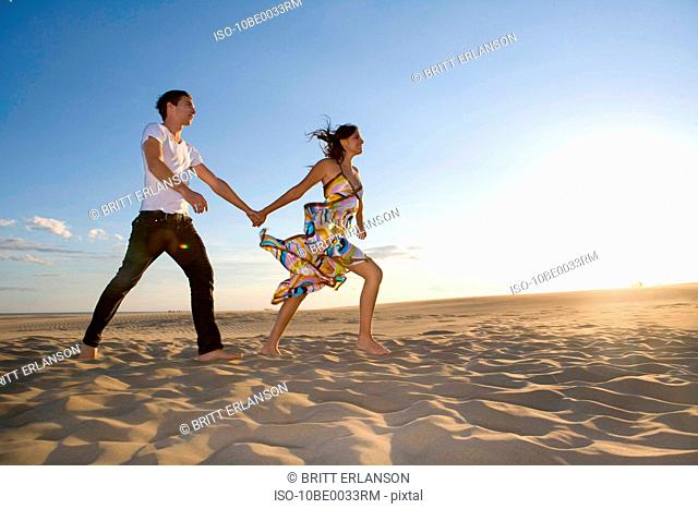 Young couple walk in sand