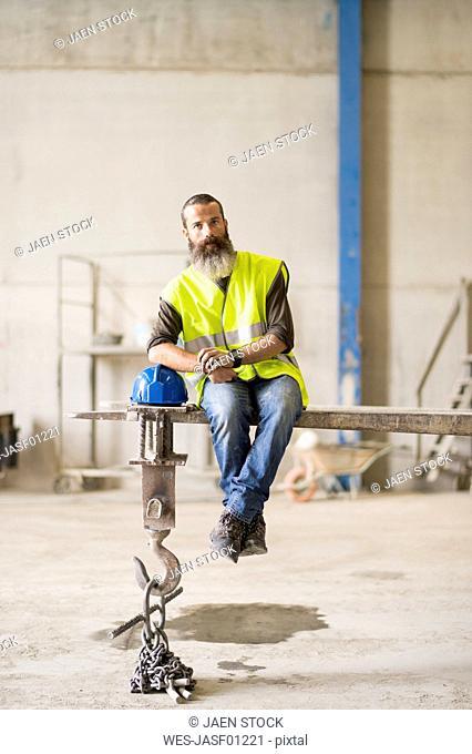 Bearded worker sitting on forklit shovel