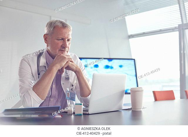 Medical scientist working at laptop in hospital conference room