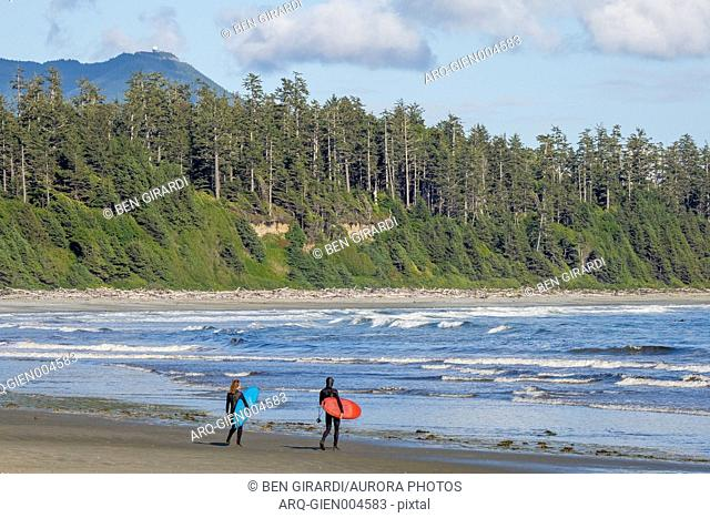 Two surfers in thick wetsuits prepare to enter the water at Florencia Bay in Pacific Rim Park in Tofino, British Columbia, Canada