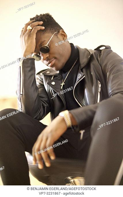 portrait of thoughtful young African man leaning head on hand, wearing christian cross necklace and sunglasses indoors in Munich, Germany