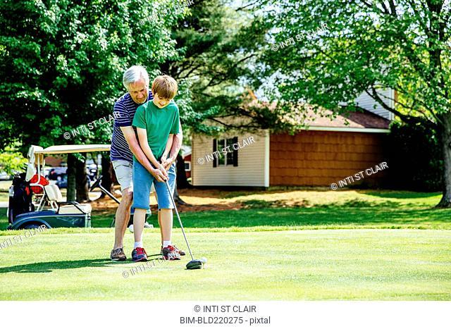 Caucasian grandfather teaching grandson golf on course