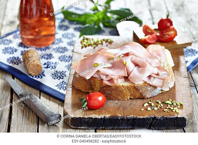 Mortadella with pistachio nuts on fresh bread slice, with cherry tomatoes, basil and rose sparkling wine