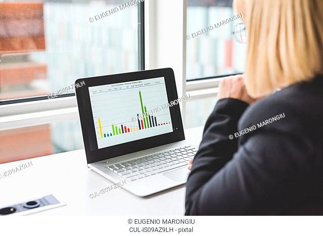 Over shoulder view of businesswoman looking at bar graph on office laptop