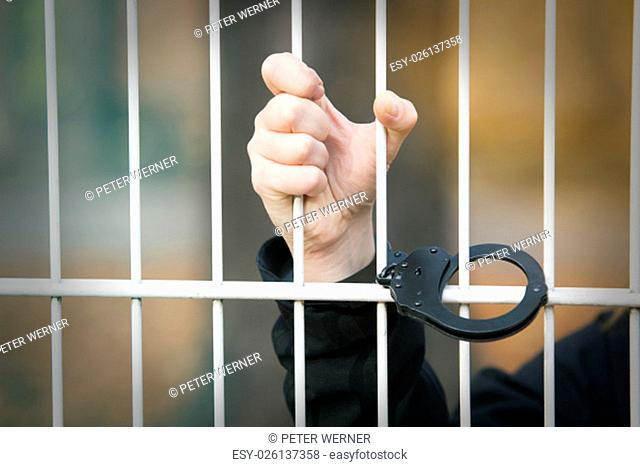 closeup of hand being handcuffed to iron bars