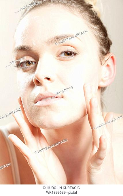 Young woman applying lotion on face, close-up