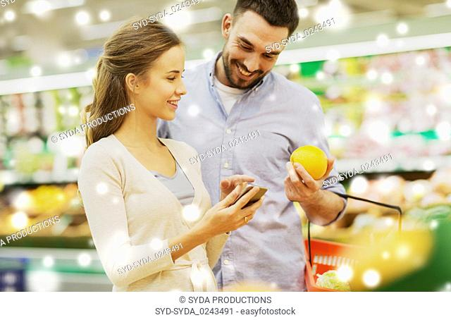 couple with smartphone buying oranges at grocery