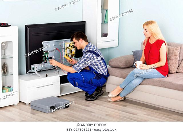 Young Woman Sitting On Couch Looking At Male Electrician Repairing Television At Home