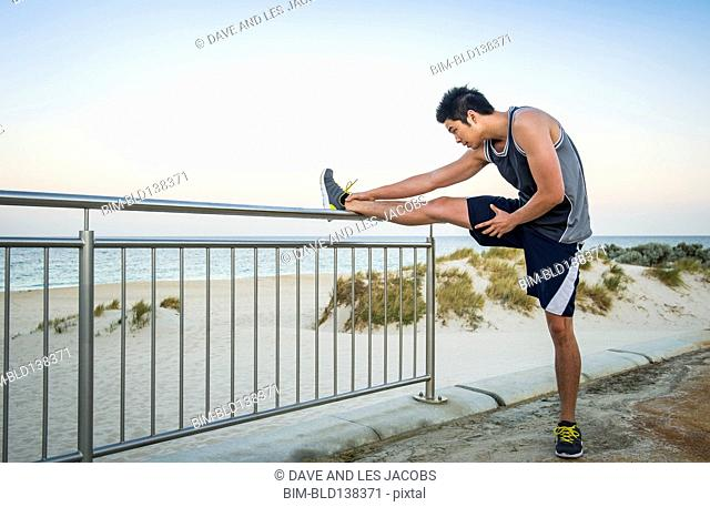 Chinese runner stretching on waterfront fence