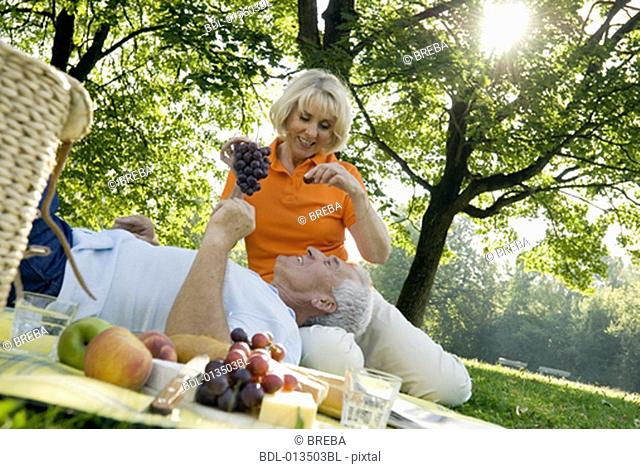 mature woman feeding husband with grapes on picnic rug