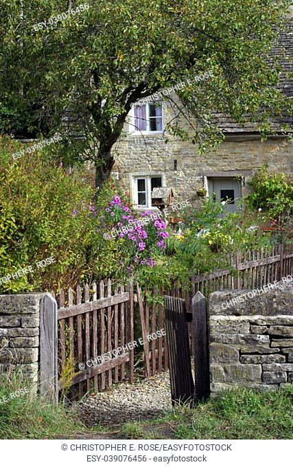 An open garden gate and pretty cottage garden in Bibury, Gloucestershire, UK