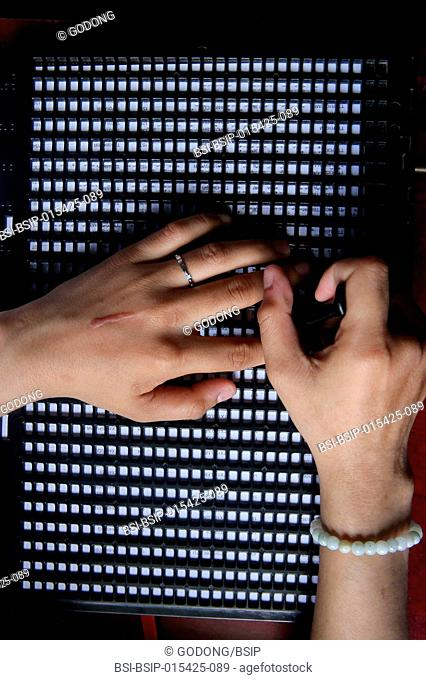 Vietnam. Center for blind children. Girl writing braille