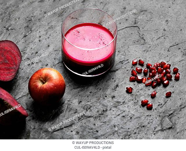 High angle view of purple raw juice, halved beetroot, apple and pomegranate seeds